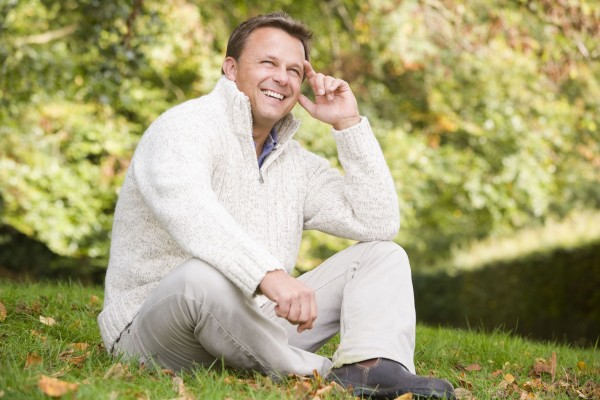 MIddle aged man sitting on grass